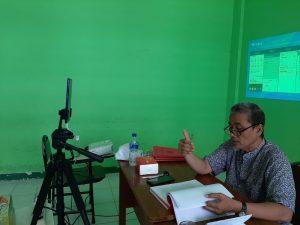 Seorang penguji skripsi online STAIl sedang menelaah skripsi dengan video call.